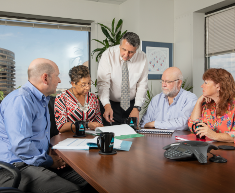 Five people in a business meeting gathered around a table